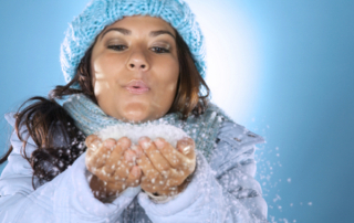 Woman blows snowflakes from her open hands