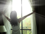 50013666 - girl opening curtains in a bedroom
